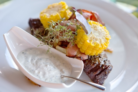 new york strip: Beef steak with garlic dip sauce garnished with corn and herbs