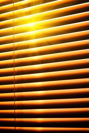 jalousie: Sun shining through yellow horizontal jalousie out of wood Stock Photo