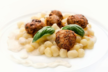 the italian dish: Gnocchi with cheese sauce and meatballs and decorated with fresh basil leaves Stock Photo