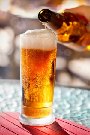 brown bottle: Pouring beer into mug from the bottle Stock Photo