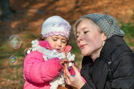 Mother and daughter blowing bubbles in the park photo