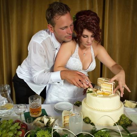 Braut und Bräutigam Anschneiden der Hochzeitstorte