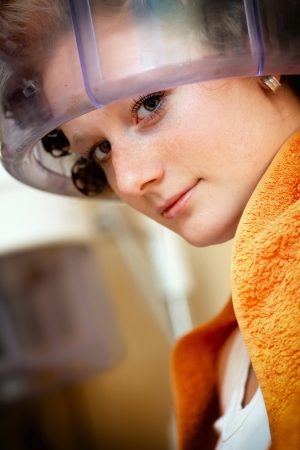 Woman drying hair at the hairdresser photo