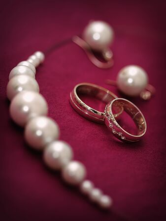 Pair of wedding rings with beads on purple background photo