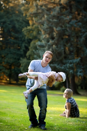 Father playing with his family in the park photo