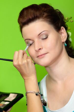 Young happy beautiful woman with makeup brush photo