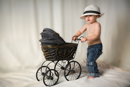 baby carriage: Little boy with antique stroller