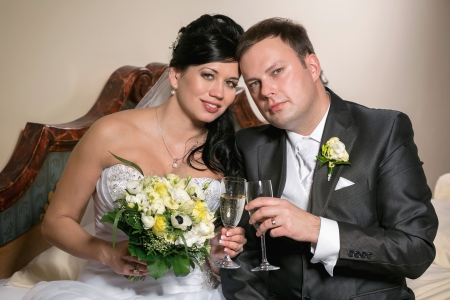 Portrait of the newlyweds on studio shooting with glasses of champagne  photo