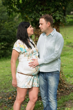 Happy pregnant woman and her husband in the park  photo