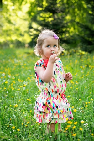 Little girl with daisy flower in hand photo