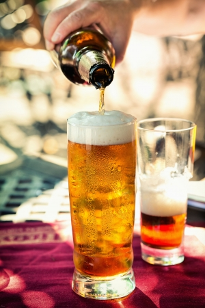 single beer bottle: Pouring beer into mug from the bottle Stock Photo