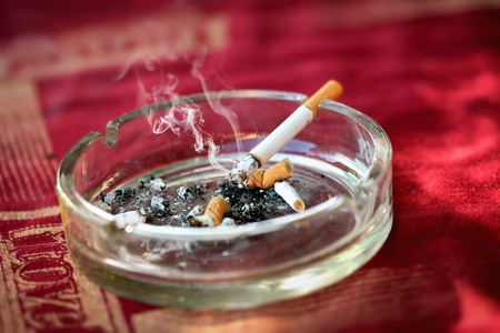 Ashtray with burning cigarette and cigarette butts photo