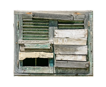 patched up: window in an old house with boarded up on white background
