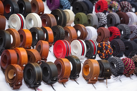 Many kinds of belts on white baskground photo