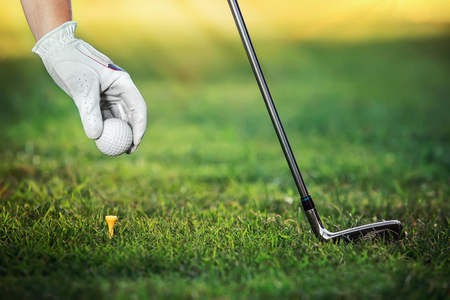 Hand golfers as gives the ground a golf ball on the tees photo