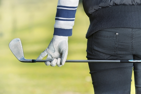 Close Up of a female golfer holding a iron behind his body photo