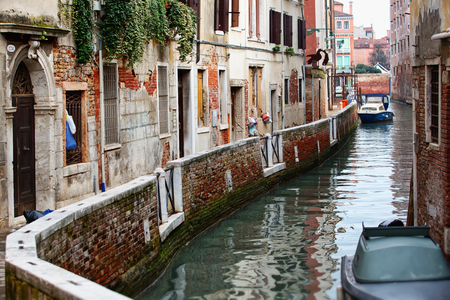 Narrow canal among old colorful brick houses in Venice, Italy  photo