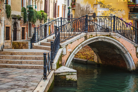 Narrow canal among old colorful brick houses in Venice, Italy.