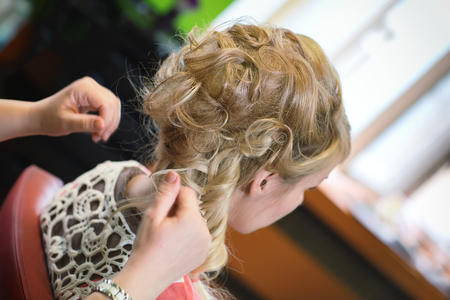 The hairdresser does a hairstyle to the bride  photo
