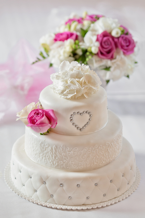 Traditional wedding cake and bridal bouquet Standard-Bild