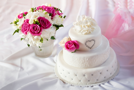Traditional wedding cake and bridal bouquet Foto de archivo