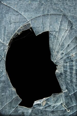 splinters: Glass cracks and  splinters with a hole on a black background Stock Photo