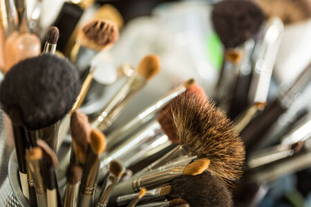 Close up view of different cosmetic brushes for makeup on a dressing table photo