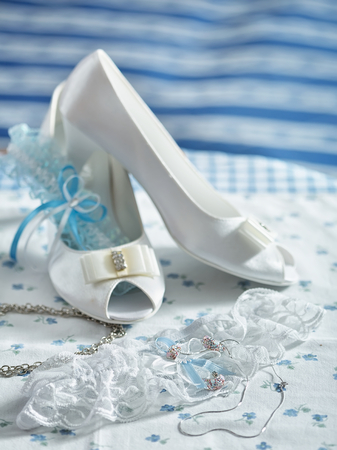 Bride shoes garter, with blue ribbon, and blue background. Closeup of wedding accessories. photo