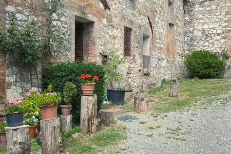 italian village: Stony antique wall with flowers in italian village, Tuscany, Chianti, Italy, Europe Stock Photo