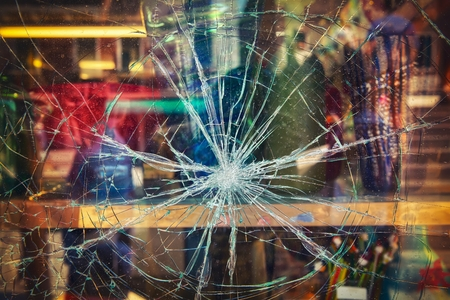 damaged: Broken shop window with color background Stock Photo