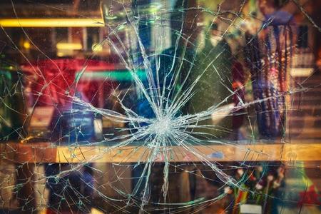 Broken shop window with color background Standard-Bild