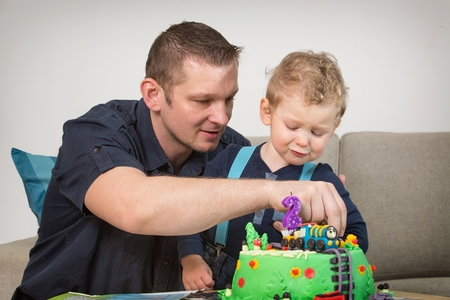 Little boy celebrating his fathers second birthday, photo