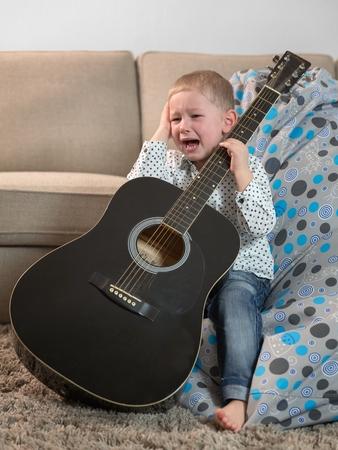 instruments de musique: Petit garçon avec une guitare et pleurer Banque d'images