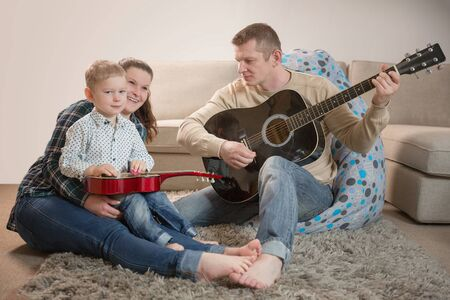 Happy family, father playing guitar at home