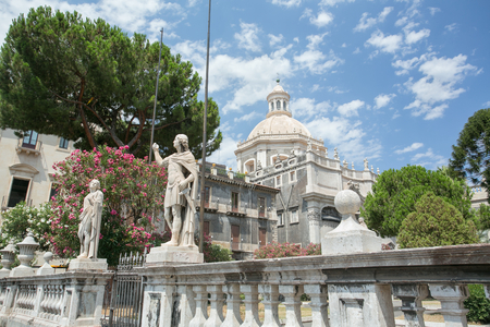 patron of europe: The Statue of St Agatha, the patron of Catania, surrounded by blooming trees of the Cathedrals garden, with the great dome of the St Agatha Abbey Church on the background, Sicily, Italy.
