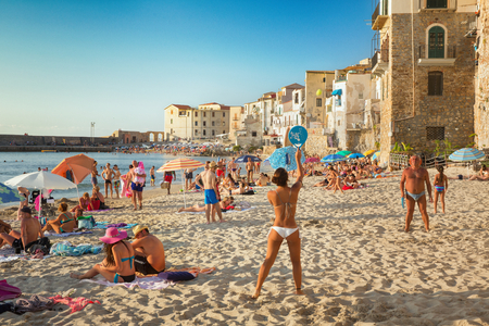 seaside resort: CEFALU,SICILY - JULY. 27. 2016: Unidentified people on sandy beach in Cefalu, Sicily, Italy at Sep 16, 2014. Cefalu is an attractive historic town and seaside resort.