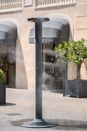 vaporized: Sprinklers splashing vaporized water at street in order to cool the hot summer temperature in Italy  Equipment, which sprayed water mist to cool down the hot summer days on the street