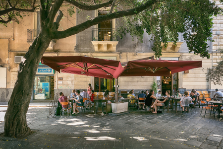 Catania, Sicily, ITALY - JUNE 25 2016 People sitting on the street in the shade under a large tree at the outdoor restaurant Editorial