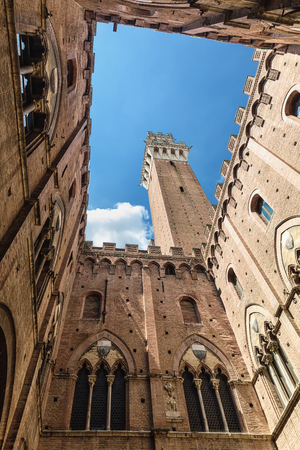 old brick wall: Siena landmark photo. Cortile del Podesta courtyard, Torre del Mangia tower and Palazzo Pubblico building. Bottom view. Tuscany, Italy Stock Photo