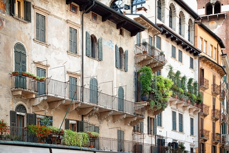 iron curtains: Beautiful balcony with flowers draping over the edge in Italy.