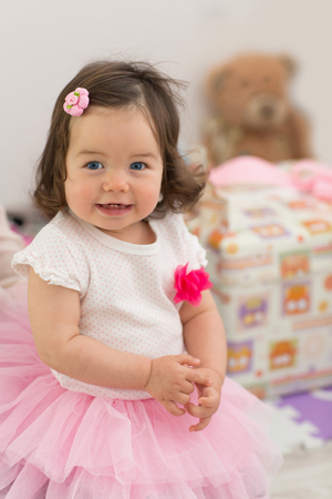 Baby in a dress, in a pink skirt. Birthday, one year