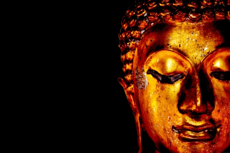 Old golden Buddha statue on a black background. photo