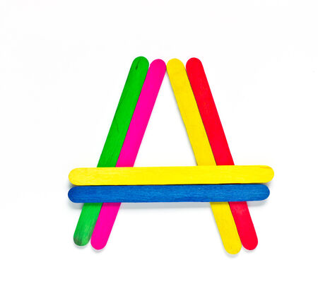 colorful wood ice-cream stick to create A  on white background. photo