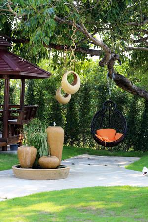 Cuscino arancione su altalena moderno in giardino. Archivio Fotografico - 49027494