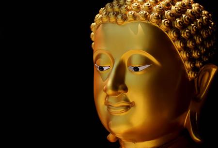 buddha statue: Gold face Buddha statue on black background.