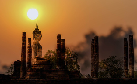 Sukhothai old historic town and old Buddha statue on sunset.