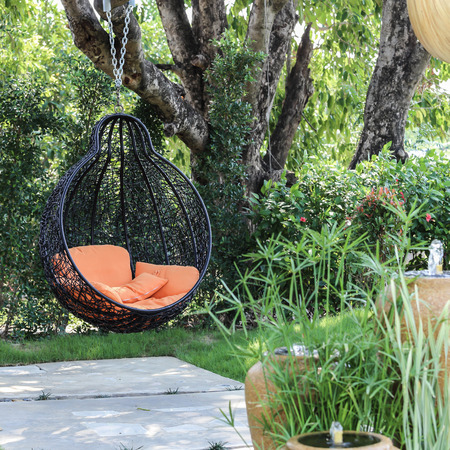 Orange pillow on modern swing in the garden.