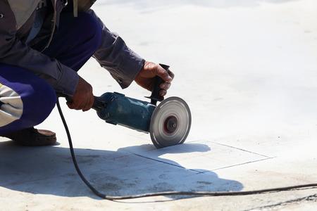 Arbeiter wurden Schneiden Zementboden.