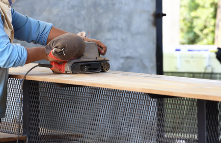 wood planer: Workers are polishing wood with electric planer. Stock Photo
