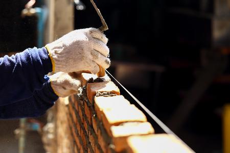 Les travailleurs de maçonnerie brique d'argile au mur.